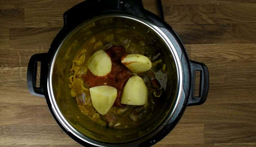 Pressure Cooker Curry Goat Recipe (Instant Pot Goat Curry): add in curry ingredients, goat shoulder, tomato paste, quartered potatoes in Instant Pot Electric Pressure Cooker