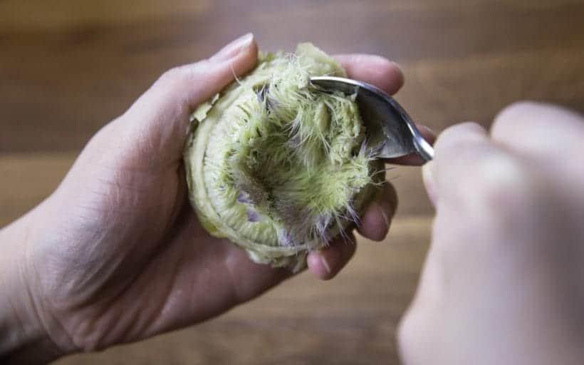 How to eat an artichoke: scrape out the inedible choke covering the artichoke heart