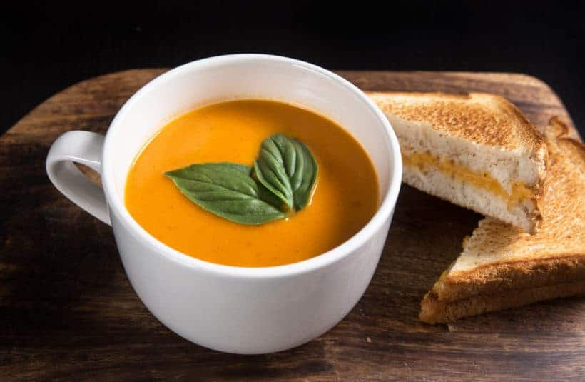 Make this Delicious Creamy Comfort: Instant Pot Tomato Soup Recipe (Pressure Cooker Tomato Soup)! This homemade tomato basil soup from scratch (with vegan option) is healthy, super easy to make, and freezer-friendly. Perfect dip for the toasted golden grilled cheese.