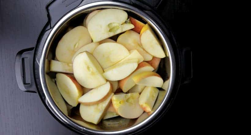 Instant Pot Apple Butter Recipe (Pressure Cooker Apple Butter): place spices and quartered apples in Instant Pot Electric Pressure Cooker.
